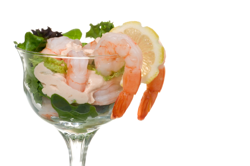 Closeup of delicious Prawn Cocktail. Fresh jumbo shrimps, cream, lettuce leaves, lemon wedge and zesty sauce. Appetizer served in cocktail glass. Copyspace.